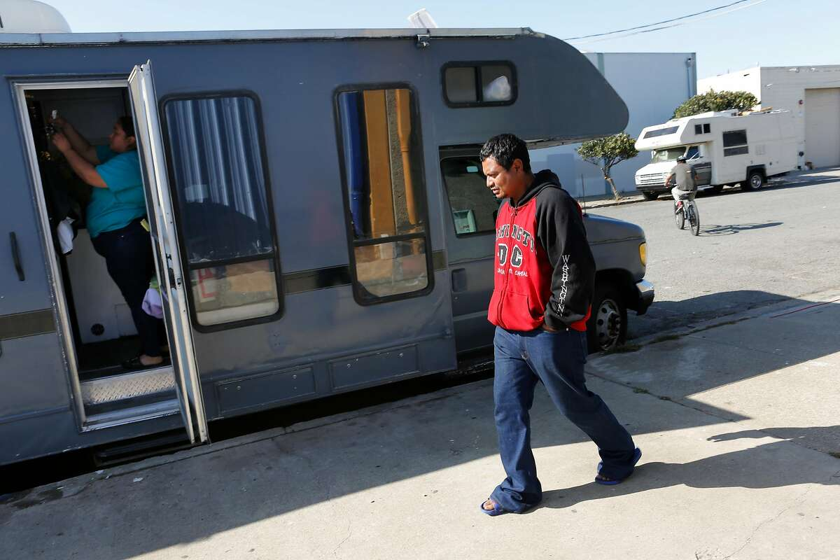 From left: Erika tidies up as her partner Edwin heads back into their RV in the Bayview neighborhood on Wednesday, Oct. 17, 2018, in San Francisco, Calif.