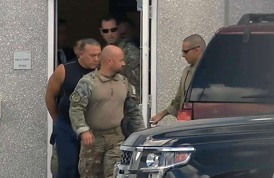 This frame grab from video provided by WPLG-TV shows FBI agents escorting Cesar Sayoc, in sleeveless shirt, in Miramar, Fla., on Friday, Oct. 26, 2018. Sayoc is an amateur body builder and former male stripper, a loner with a long arrest record who showed little interest in politics until Donald Trump came along. On Friday, he was identified by authorities as the Florida man who put pipe bombs in small manila envelopes, affixed six stamps and sent them to some of Donald Trump's most prominent critics. (WPLG-TV via AP) Photo: Associated Press