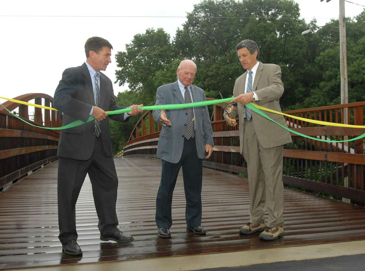 In this file photo then Hamden Mayor Craig Henrici and then state Sen. Joseph J. Crisco hold the ribbon as David Schaefer, then chairman of the Farmington Canal Greenway Commission in Hamden, cuts it.