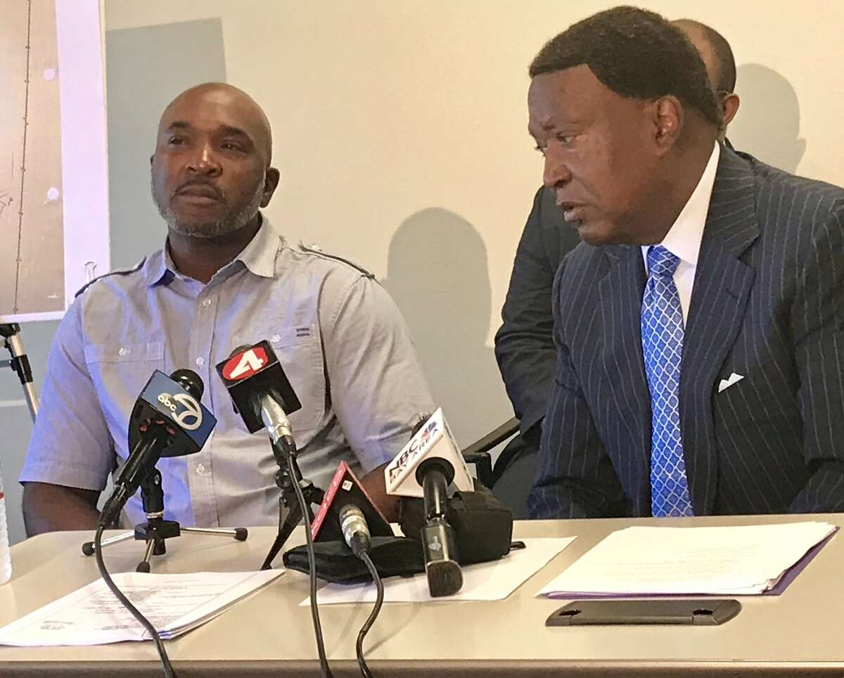 Lawrence Haley, left, speaks alongside his attorney John Burris about the racism he experienced while working as a plumber on a Clark Construction site at 150 Van Ness in San Francisco.