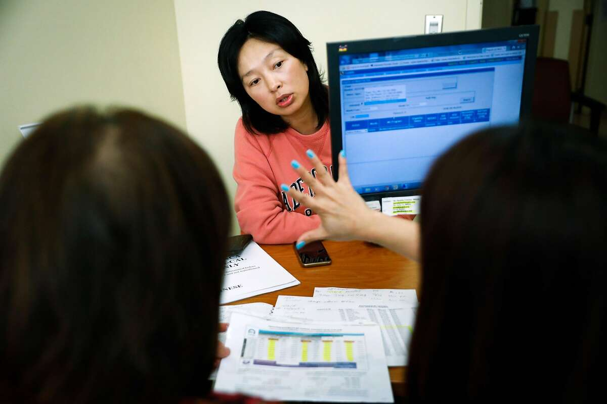 Ye Yuan (C) gets assistance with her healthcare plan from Human Services Specialists Connie Chung (R) and Bier Liang (L) at La Clinica health clinic in Oakland, California, on Thursday, Oct. 25, 2018.