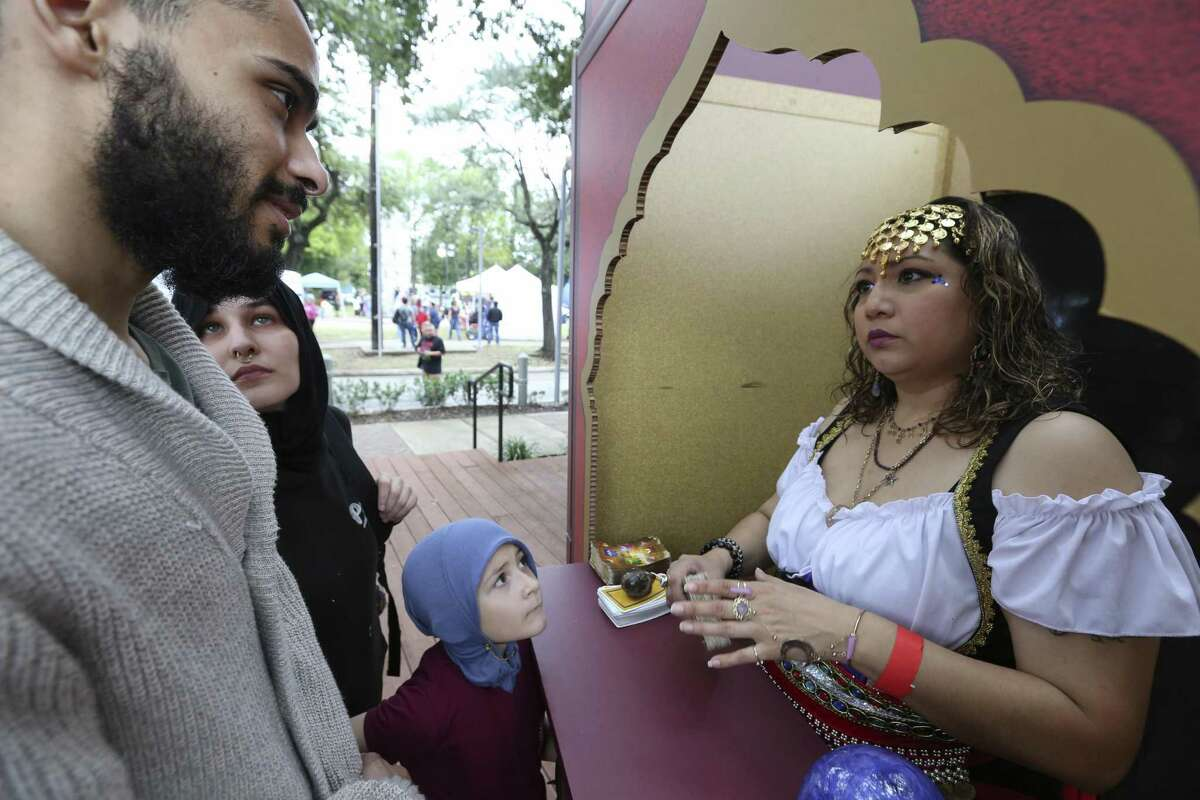 Psychic Victoria Alvarado reads fortune for Ahmed and Hayaam Aldawsari and their daughter, Hayati, 6, at the East End Street Fest on Saturday, Oct. 20, 2018, in Houston.