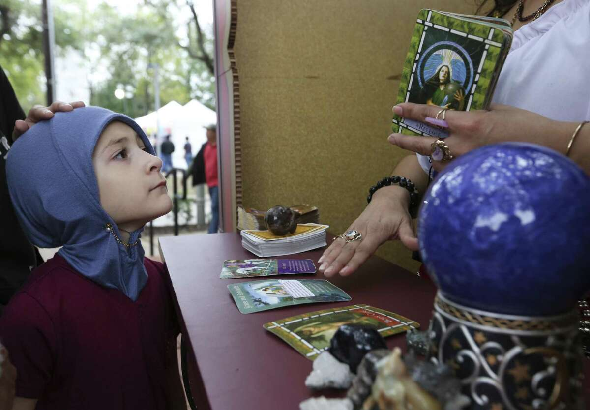 Hayati Aldawsari, 6, watches psychic Victoria Alvarado's cards as Alvarado reads fortune for her parents Ahmed and Hayaam Aldawsari at the East End Street Fest on Saturday, Oct. 20, 2018, in Houston.