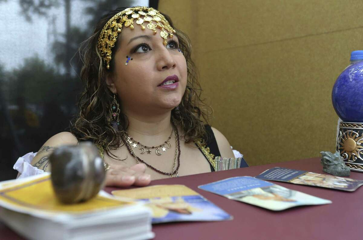 Psychic Victoria Alvarado reads fortune for people from her booth at the East End Street Fest on Saturday, Oct. 20, 2018, in Houston.