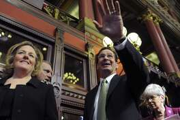 Connecticut Gov. Dannel P. Malloy waves after presenting his two-year budget, during a joint session of the General Assembly with his wife Cathy, left, and Lt. Gov. Nancy Wyman, right, at his side, at the Capitol, in Hartford, Conn., Wednesday, Feb. 16, 2011.