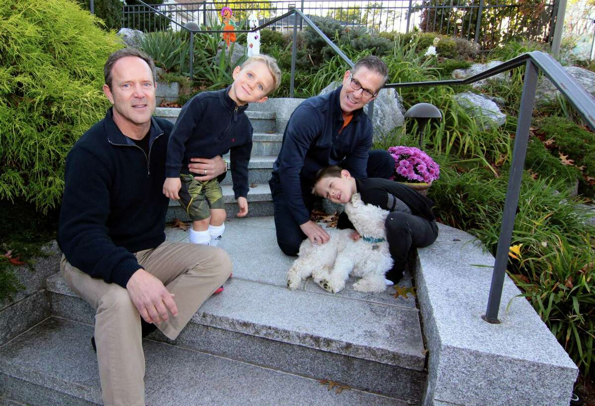 Greg Zola, at left, and his husband, Dr. Mark Leondires, with their children Owen, 5, and Luke, 7, at right with their pet Belle at their home in Westport Wednesday.