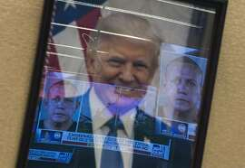 Mugshots of bombing suspect Cesar Sayoc are reflected on a portrait of US President Donald Trump prior to a press conference at the Department of Justice in Washington, DC on October 26, 2018, following the arrest of Sayoc in Florida. - The suspect has been charged with five federal crimes in connection with more than a dozen suspicious packages sent in a US mail bombing spree, Sessions said. (Photo by ANDREW CABALLERO-REYNOLDS / AFP)ANDREW CABALLERO-REYNOLDS/AFP/Getty Images