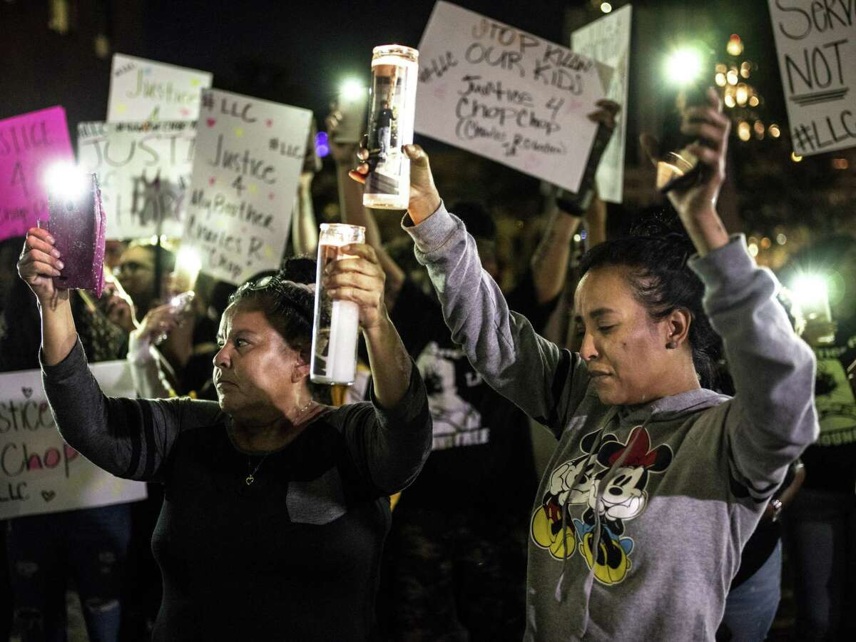 Patricia Slack, mother of Charles Roundtree Jr., right, and Arlene Castillo, grandmother to Roundtree, left, raise their candles together during a protest outside of the San Antonio Police's Public Safety Headquarters on Friday, October 26, 2018. The protest is being held to call attention to the death of 18-year-old Charles