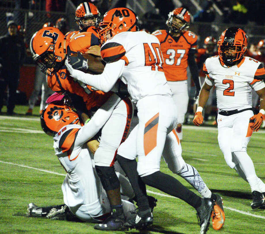 Edwardsville's Adam Foster (No. 40) leads a group effort to bring down the Evanston ball carrier.