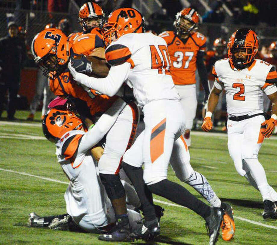 Edwardsville's Adam Foster (No. 40) leads a group effort to bring down an Evanston ball carrier Friday night in a Class 8A playoff game in Evanston.. Photo: Matt Kamp | For The Telegraph