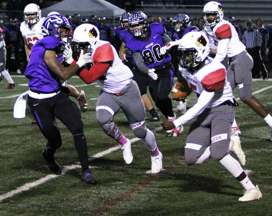Alton's Tim Johnson (right) shoots through a hole off the block from Lonnie Tate for a 73-yard touchdown run that was called back by a holding penalty in the first quarter Friday night in Rolling Meadows. Photo: Greg Shashack | The Telegraph