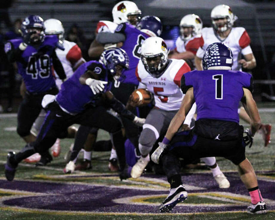 Alton's Tim Johnson looks to split a pair of Mustangs defenders in Friday's Class 7A playoff game in Rolling Meadows. The unbeaten Mustangs staved off Alton's upset bid to win 29-27. Alton closes its season at 5-5. Photo: Greg Shashack / The Telegraph