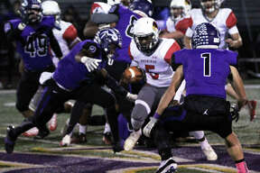 Alton's Tim Johnson looks to split a pair of Mustangs defenders in Friday's Class 7A playoff game in Rolling Meadows. The unbeaten Mustangs staved off Alton's upset bid to win 29-27. Alton closes its season at 5-5.