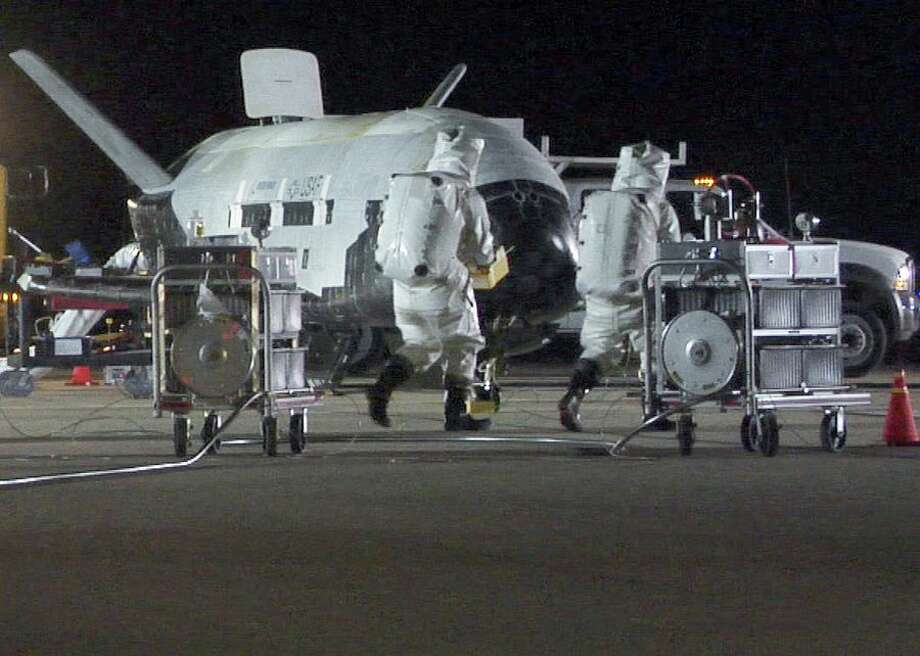 Technicians in self-contained protective suits close in on the X-37B for initial checks on that December 2010 night. The space plane bears a striking resemblance to the much larger space shuttles, and for a reason -- they share a common heritage in NASA's work on lifting-body vehicles. In fact, the X-37 initially was a NASA project that ran from 1999 through 2004, though the space agency never got as far as building that orbital vehicle. The Air Force and Boeing picked up where NASA left off to build the X-37B. Photo: CBSI/CNET