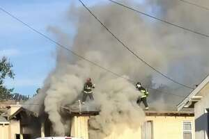 Alameda County firefighters pulled a man from a house fire Friday in San Leandro.