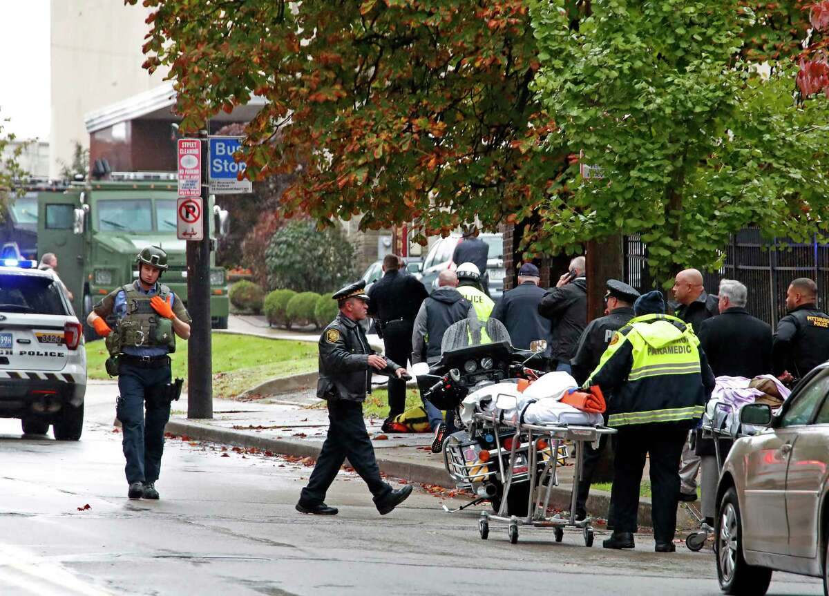 First responders surround the Tree of Life Synagogue, rear center, in Pittsburgh, where a shooter opened fire Saturday, Oct. 27, 2018, wounding three police officers and causing