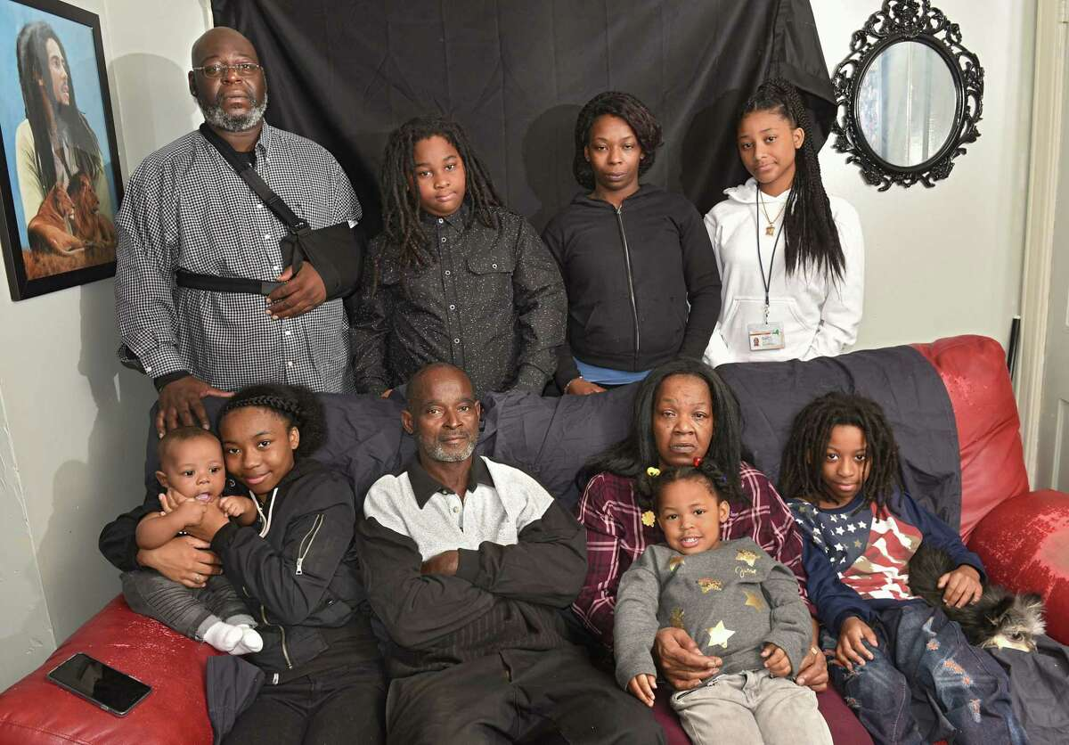 The Graham family, top row from left, Richard Kirk, Alondion, Shirley, Rahmera; bottom row from left, Kushariah holds Rahzeer, 5 mos., Jerome Johnson, Lenora holds Rahleeyah, 3, and Massiah holds dog Wolfie, on Friday Oct. 26, 2018 in Albany, N.Y. The Grahams had their home destroyed last weekend when a city contractor took out its wall while demolishing another. They are staying at a friend's apartment. (Lori Van Buren/Times Union)