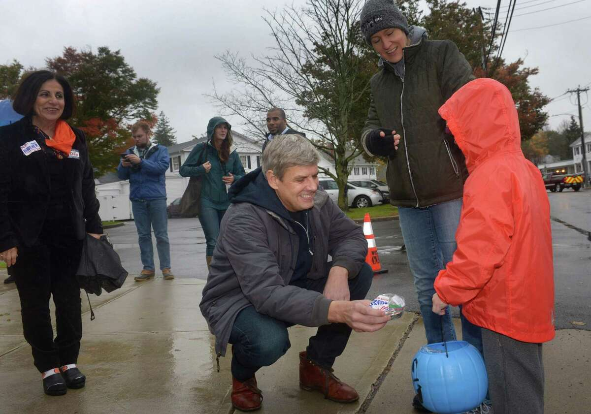 Republican gubernatorial candidate Bob Stefanowski gives Halloween candy to Wilton resident Riley Metz while his mom Susi Metz, looks on Saturday in Wilton.