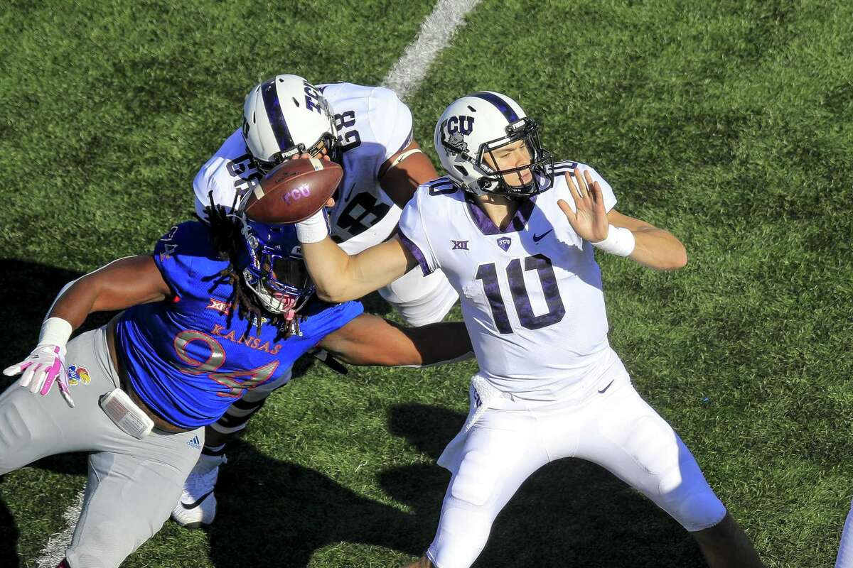 New Canaan grad Michael Collins of the TCU Horned Frogs passes under pressure from Codey Cole (94) of the Kansas Jayhawks during the second quarter at Memorial Stadium on Saturday in Lawrence, Kan. Collins went 23 for 33 for 351 yards with a touchdown in the 27-26 loss.