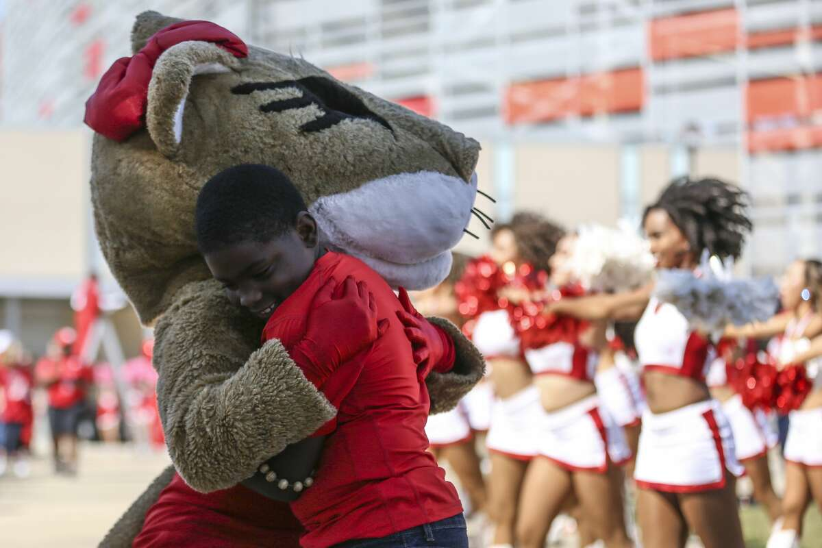 A young boy hugs Shasta the mascot before the Houston Cougars take on the South Florida Bulls at TDECU Stadium Saturday, Oct. 27, 2018, in Houston.