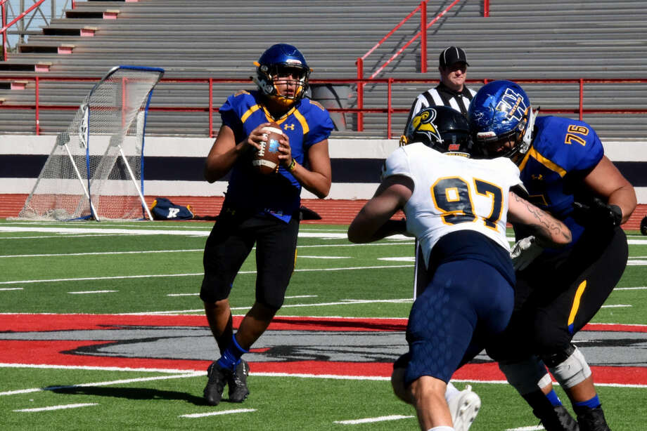 Wayland Baptist Pioneers sophomore quarterback Nick Quintero (left) drops back to pass during the Pioneers' Sooner Athletic Conference football game against Texas Wesleyan. Pioneers senior offensive lineman Eric Lunsford (76) tries to keep the Rams' junior defensive lineman Ryan Leichus away. Photo: Claudia Lusk/Wayland Baptist University