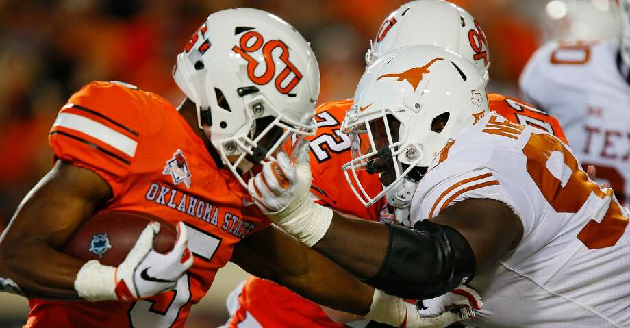 STILLWATER, OK - OCTOBER 27:  Running back Justice Hill #5 of the Oklahoma State Cowboys gets his facemask pulled by defensive lineman Chris Nelson #97 of the Texas Longhorns for a penalty in the second quarter on October 27, 2018 at Boone Pickens Stadium in Stillwater, Oklahoma.  Oklahoma State leads 31-14 at the half. (Photo by Brian Bahr/Getty Images) Photo: Brian Bahr/Getty Images