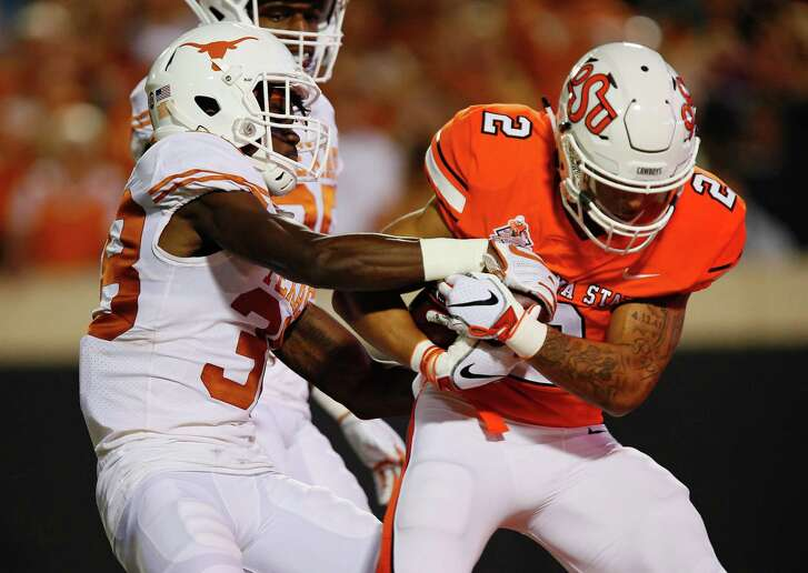 Oklahoma State receiver Tylan Wallace, right, pulls away from Texas defensive back Kobe Boyce to score the game's first TD.