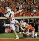 Texas quarterback Sam Ehlinger (11) scores after escaping from Oklahoma State's Kenneth Edison-McGruder. For a game recap, go to houstonchronicle.com/sports.