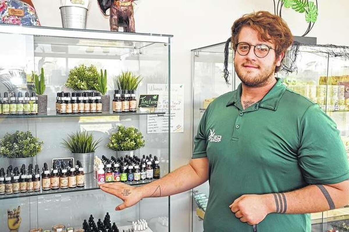 Dustin Hays shows some of the hemp-based CBD oil products sold at the CBD Shop in Alton.