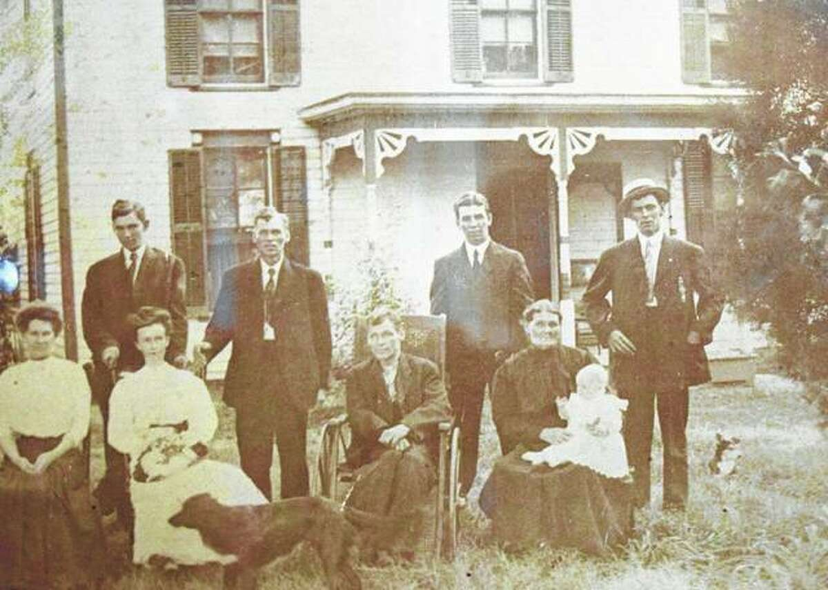 Members of the Carrigan family stand in front of the house on their farm.