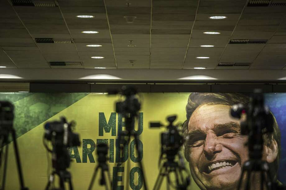 Cameras and tripods stand in front of a banner featuring Jair Bolsonaro, presidential candidate for the Social Liberal Party, in Rio de Janeiro. Photo: Dado Galdieri, Bloomberg / © 2018 Bloomberg Finance LP