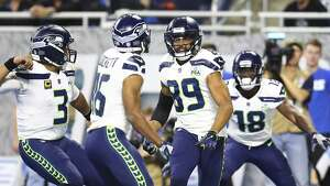 Seattle Seahawks wide receiver Doug Baldwin (89) runs to wide receiver Tyler Lockett (16) after Lockett's 24-yard touchdown reception during the first half of an NFL football game against the Detroit Lions, Sunday, Oct. 28, 2018, in Detroit. (AP Photo/Rey Del Rio)