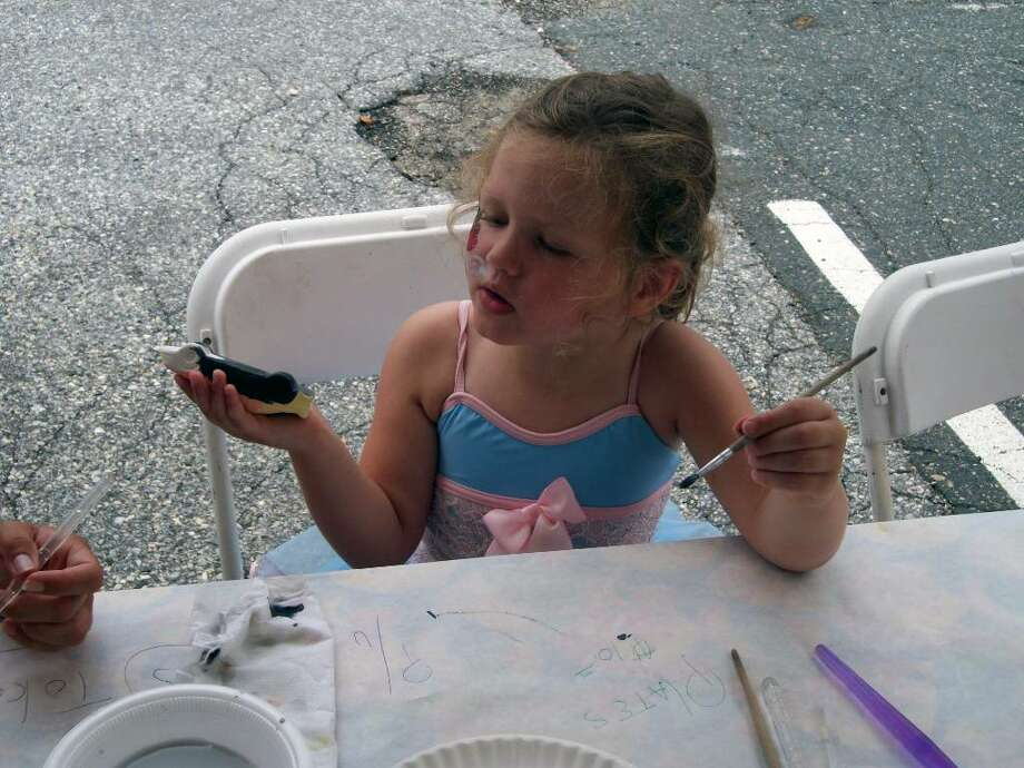 Caroline Young, 3, paints a car at Hands On Pottery during the opening day of Family Fun Days, a three-day event sponsored by the Darien Chamber of Commerce. Photo: Maggie Gordon / Darien News