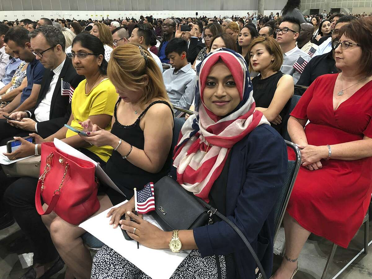 In this Sept. 18, 2018 photo Sameeha Alkamalee Jabbar, a 38-year-old from Orange County sits during a naturalization ceremony in Los Angeles. Alkamalee Jabbar who is originally from Sri Lanka, said the process took ten months and at times she worried but knew about the backlog. More than 700,000 immigrants are waiting on their applications to become U.S. citizens, a process that in many parts of the country now takes a year or more. (AP Photo/Amy Taxin)