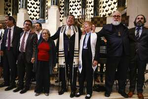 Interfaith leaders sing together at the end of a gathering at Temple Emanu-El in San Francisco marking the synagogue slayings in Pittsburgh.