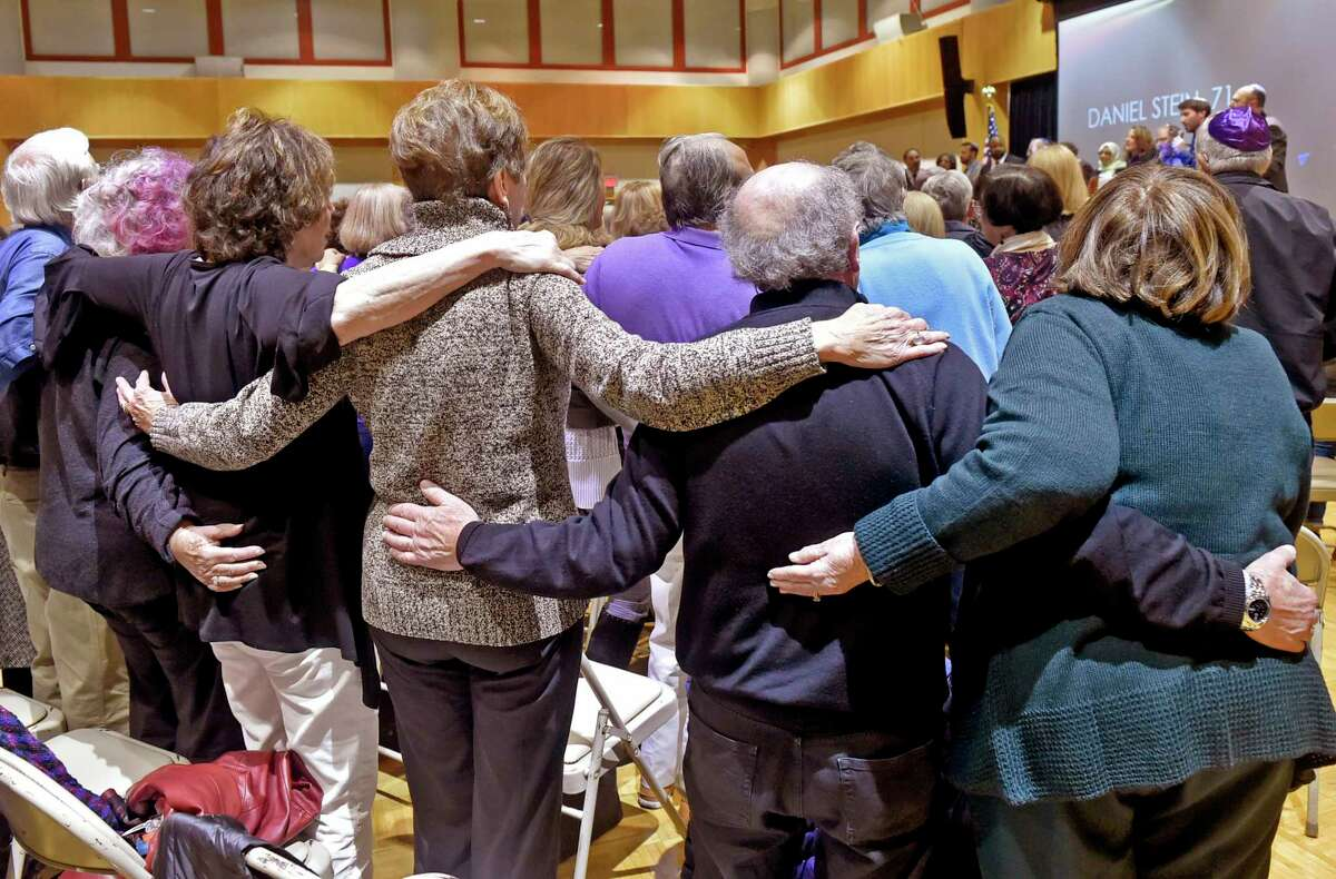 Woodbridge, Connecticut - Sunday, October 28, 2018: During a stirring prayerful song, the crowd embraces each other at the conclusion of a vigil held in response to the Pittsburgh Synagogue shooting Saturday at the Jewish Community Center in Woodbridge Sunday evening. The vigil was sponsored by the Jewish Federation of Greater New Haven.