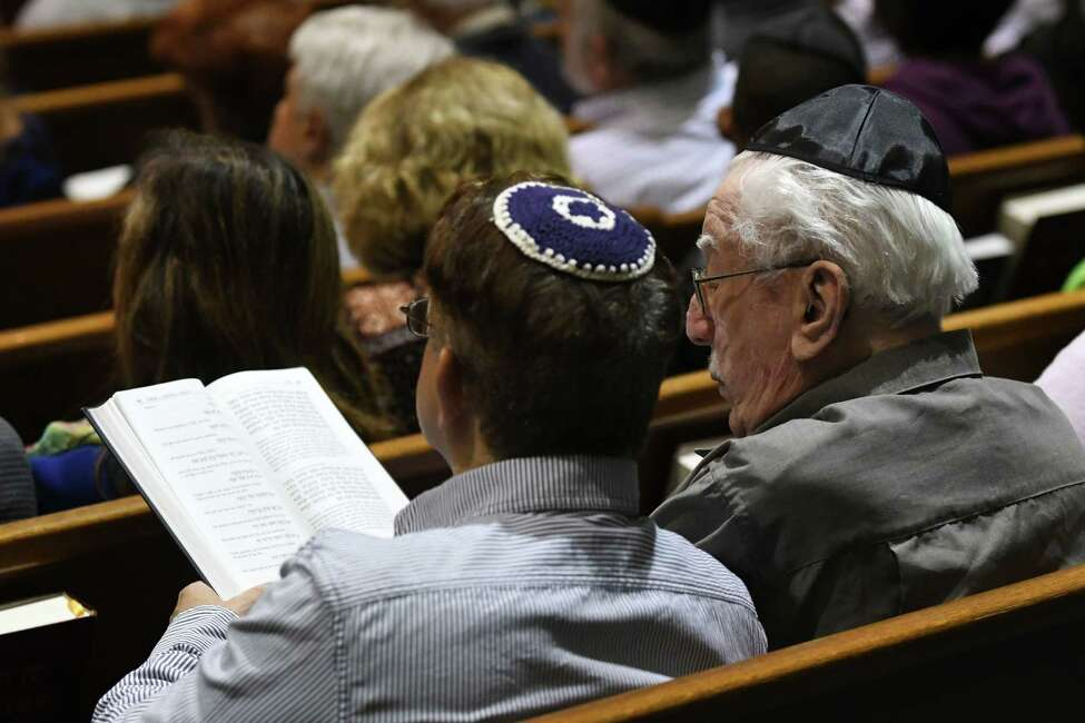 Johnathan Eisenberg, left, and his uncle, Abraham Staff, 99, right, join in prayer for the victims of the Pittsburgh synagogue shooting on Sunday, Oct. 28, 2018, during a community prayer service at Temple Israel in Albany, N.Y. (Will Waldron/Times Union)
