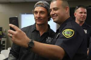 HOUSTON, TX - OCTOBER 28:  Matthew McConaughey (L) takes photos with Houston's Police Department officer during Wild Turkey gives back 2018 with Matthew McConaughey on October 28, 2018 in Houston, Texas.