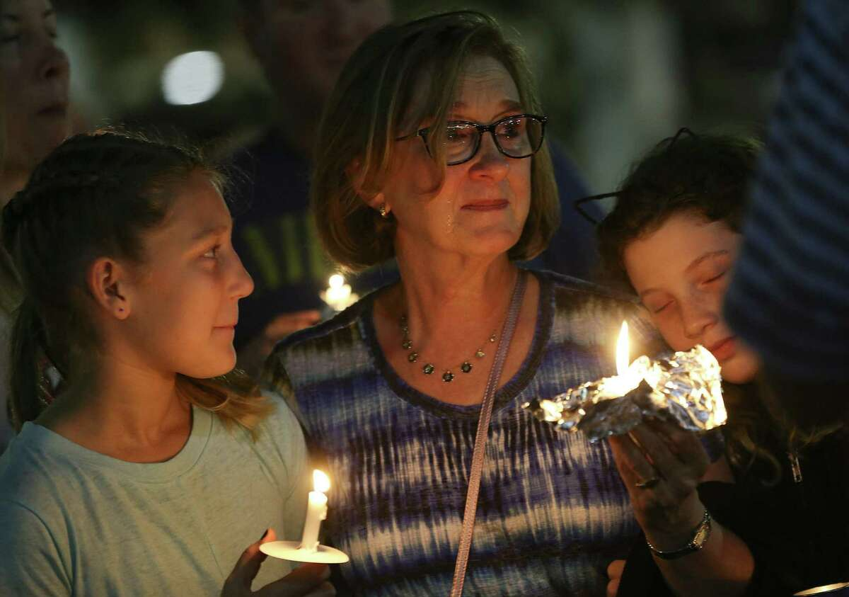 Carly Ostrin, 10, looks at her grandmother, Olivia, with Lila Ostrin, 10, during a vigil on Sunday, October 28, 2018, at the Evelyn Rubenstein Jewish Community Center to honor the victims of the Pittsburgh synagogue attack.