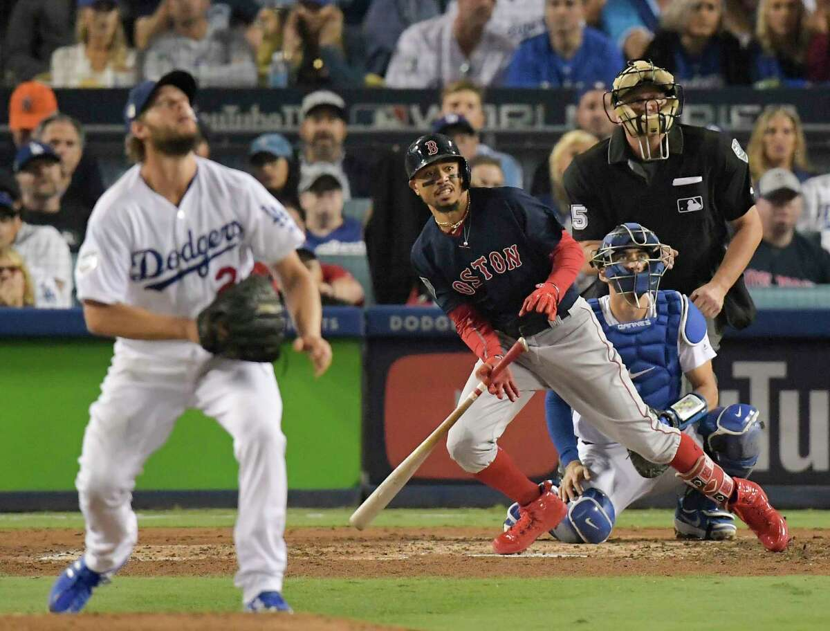 Boston Red Sox's Mookie Betts, right, watches his home run off Los Angeles Dodgers starting pitcher Clayton Kershaw during the sixth inning in Game 5 of the World Series baseball game on Sunday, Oct. 28, 2018, in Los Angeles.