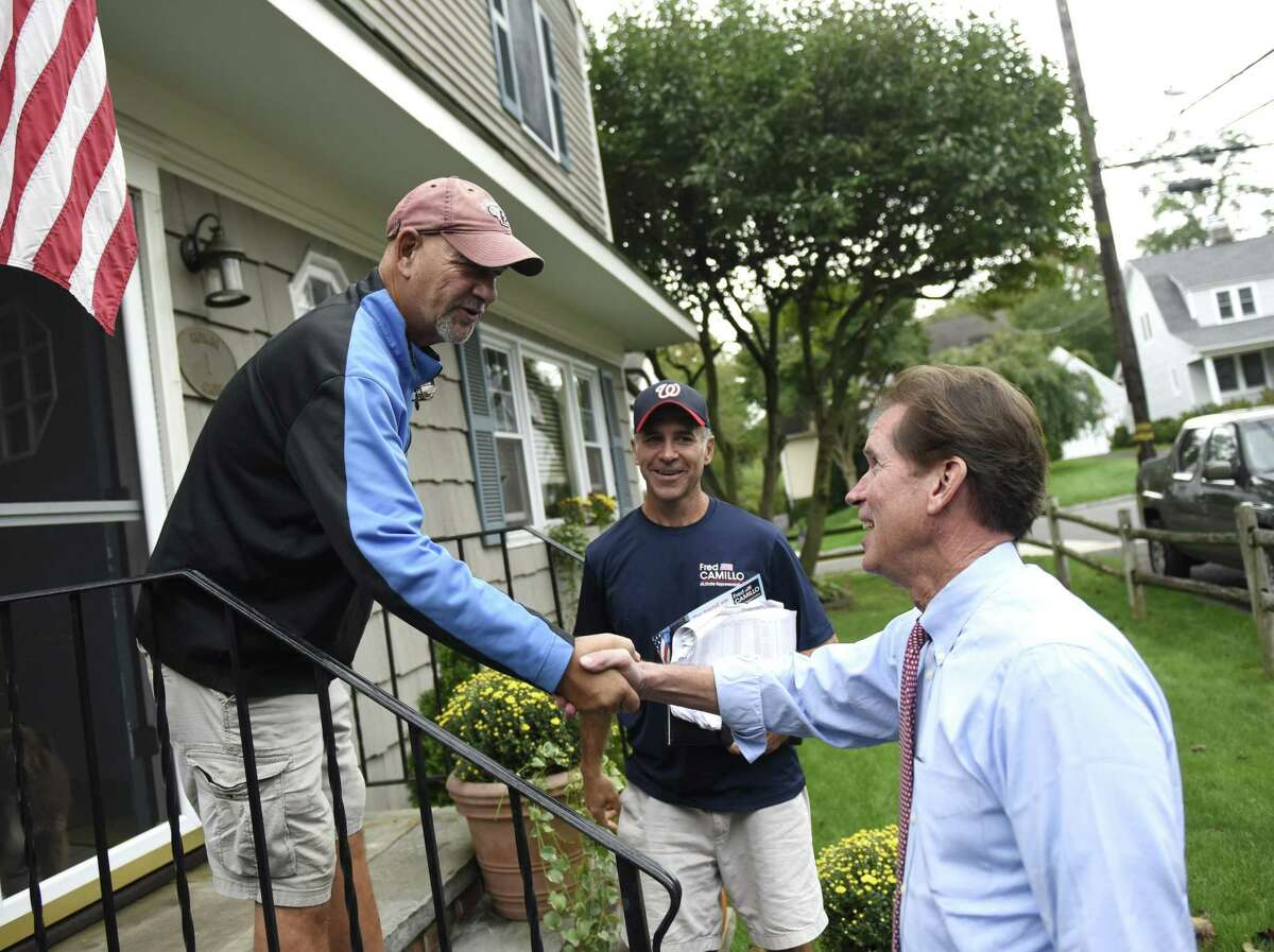 State Sen. L. Scott Frantz, R-Greenwich, shakes hands with Rick Capalbo while canvassing with state Rep. Fred Camillo, R-Greenwich, in the Cos Cob section of Greenwich, Conn. Tuesday, Oct. 9, 2018.