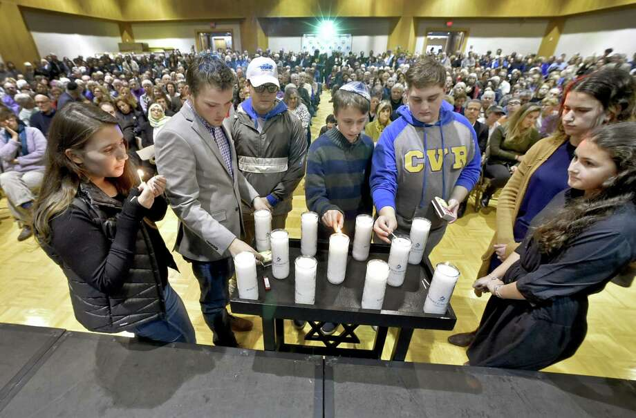 Representatives from the International Jewish Teen Youth Group light candles on Sunday in memory of those lost in Saturday's Pittsburgh synagogue shooting during a vigil at the Jewish Community Center in Woodbridge sponsored by the Jewish Federation of Greater New Haven. Below, Avrom Berel and partner Megan Yost of New Haven share a moment. Photo: Peter Hvizdak / Hearst Connecticut Media / New Haven Register