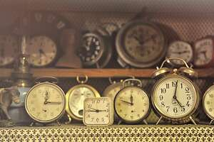 Assorted collection of old vintage alarm clocks sitting on a rustic kitchen bench.