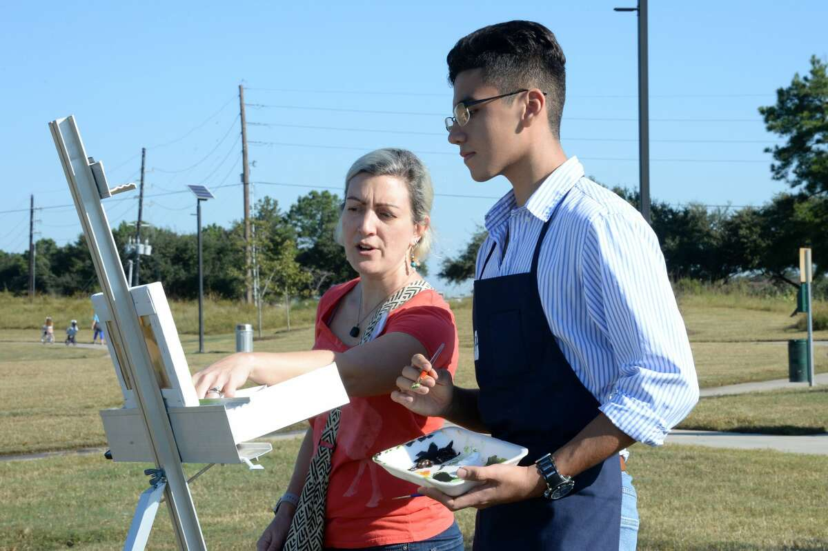 Art teacher Melissa Lobpries of Taylor High School coaches Jean Paul Fuentes of Taylor High School as he works on his entry for the Plein Air Painting Competition at Willow Fork Park, Katy, TX on Saturday, October 27, 2018.