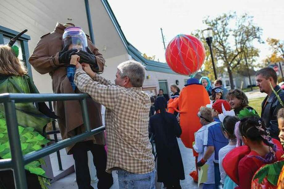 "Cale Grable, 9, dressed as the ""Headless Man,"" gets some last minute costume assistance from his dad as he awaits his turn to take the stage at the City of Edwardsville costume contest on Saturday. Photo: Marci Winters-McLaughlin 