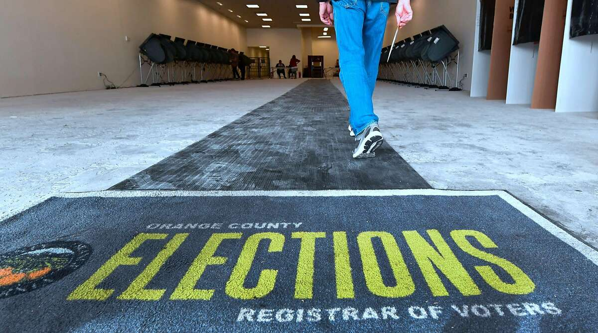 A voter holds onto his ballot while entering an Early Vote Center in Huntington Beach, California on October 27, 2018, as voting begins in the traditional Republican stronghold of Orange County. (Photo by Frederic J. BROWN / AFP)FREDERIC J. BROWN/AFP/Getty Images