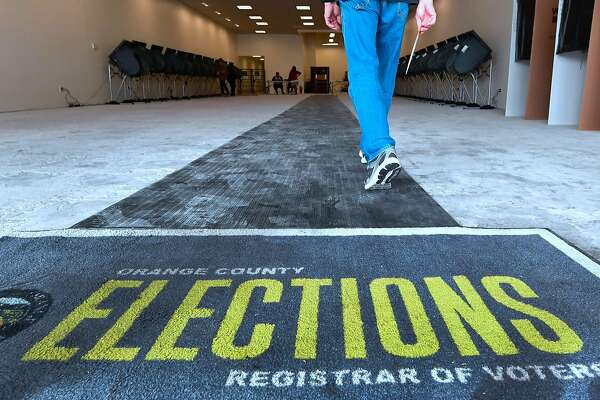 0e273b0fbf8 1of22A voter holds onto his ballot while entering an early vote center in  Huntington Beach (Orange County on Saturday.Photo  FREDERIC J.  BROWN Frederic J. ...