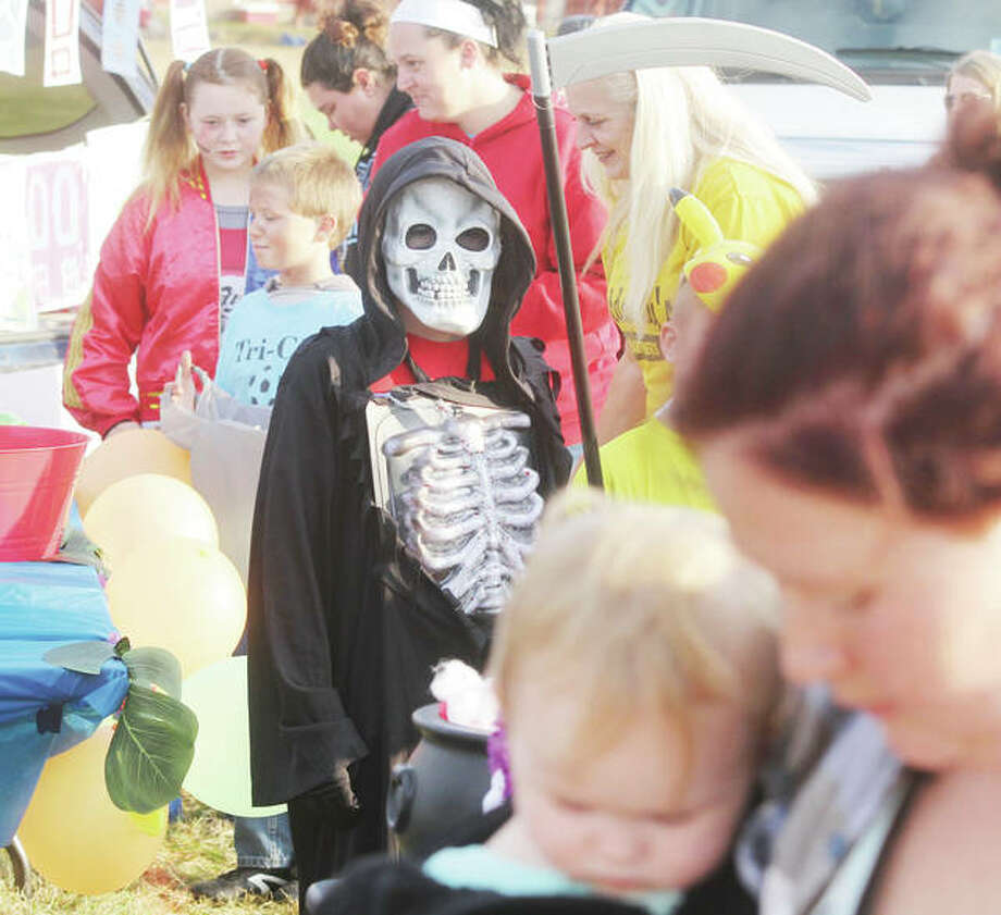 Death patiently waits for candy, and perhaps a soul or two, Saturday during a Trunk-or-Treat at the Ivy Heights Church of God in Wood River. More than 500 people came out for candy at the annual event, held in conjunction with the YWCA this year. The YWCA is planning to move it's before- and after-school program for the Roxana School District to the church as soon as DCFS gives final approval. Photo: Scott Cousins | The Telegraph