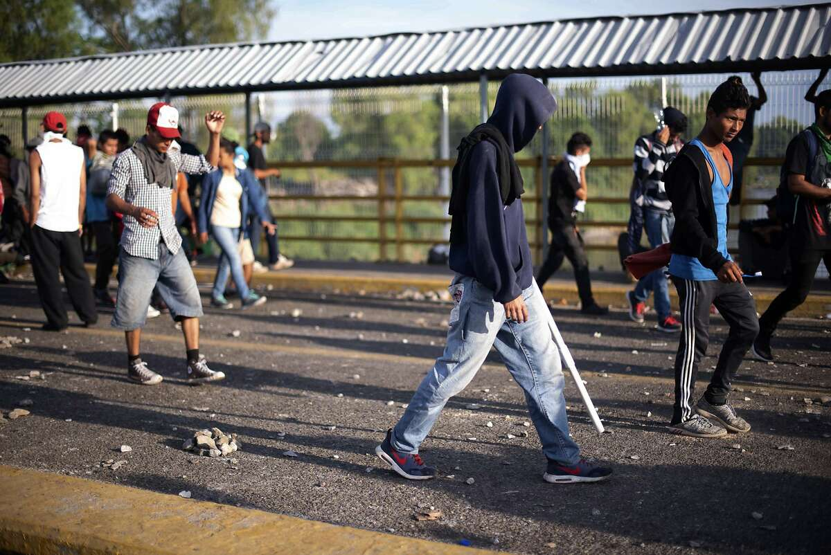Central American migrants assemble on a border bridge connecting Guatemala and Mexico, in Tecun Uman, Monday, Oct. 29, 2018. The new group of migrants, who called themselves a second caravan, gathered on the bridge after forcing their way through a gate on Sunday, at the Guatemalan end and clashed with Mexican authorities. (AP Photo/Santiago Billy)