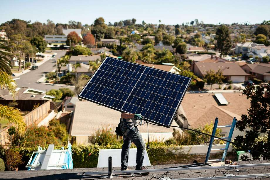 A Sunrun installer before placing a solar panel at a customer's home in Carlsbad, Calif., Oct. 18, 2018. Tesla is relying on showrooms to sell electric cars, solar roofs and batteries. But a California rival has made inroads into the residential business. (Collin Chappelle/The New York Times) Photo: Collin Chappelle / New York Times